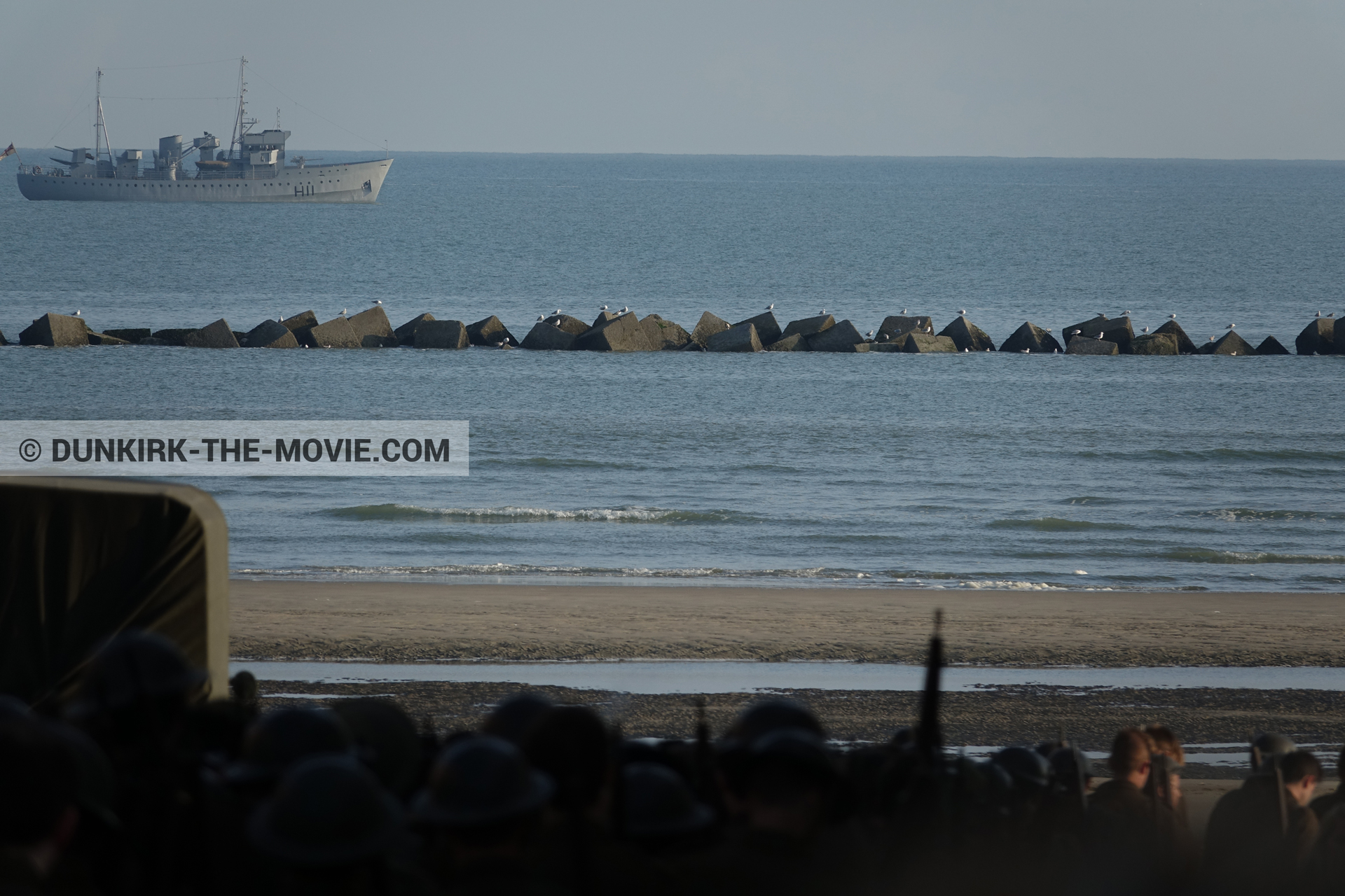 Picture with boat, truck, supernumeraries, beach,  from behind the scene of the Dunkirk movie by Nolan