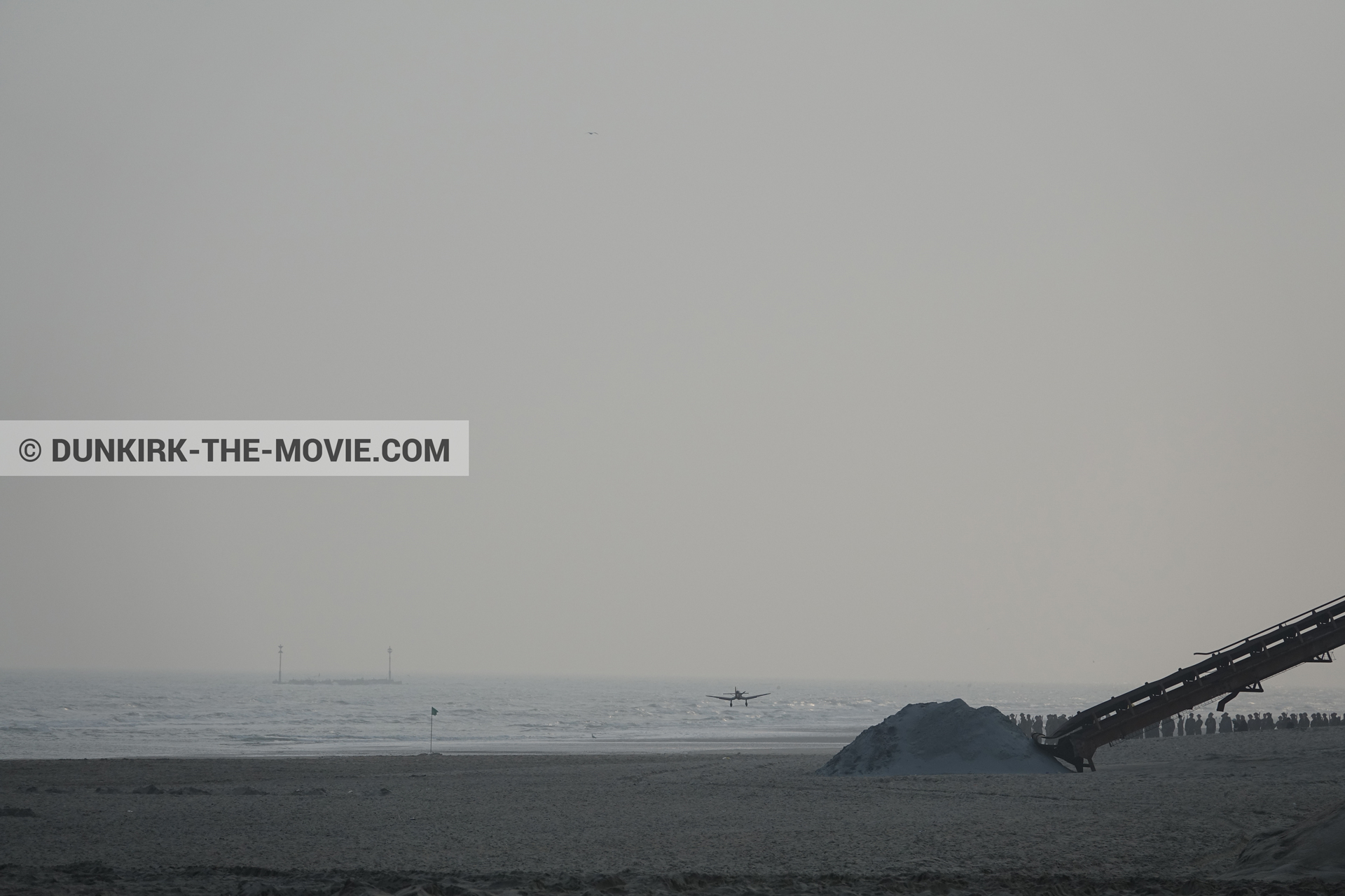 Picture with plane, grey sky, decor, supernumeraries, beach,  from behind the scene of the Dunkirk movie by Nolan