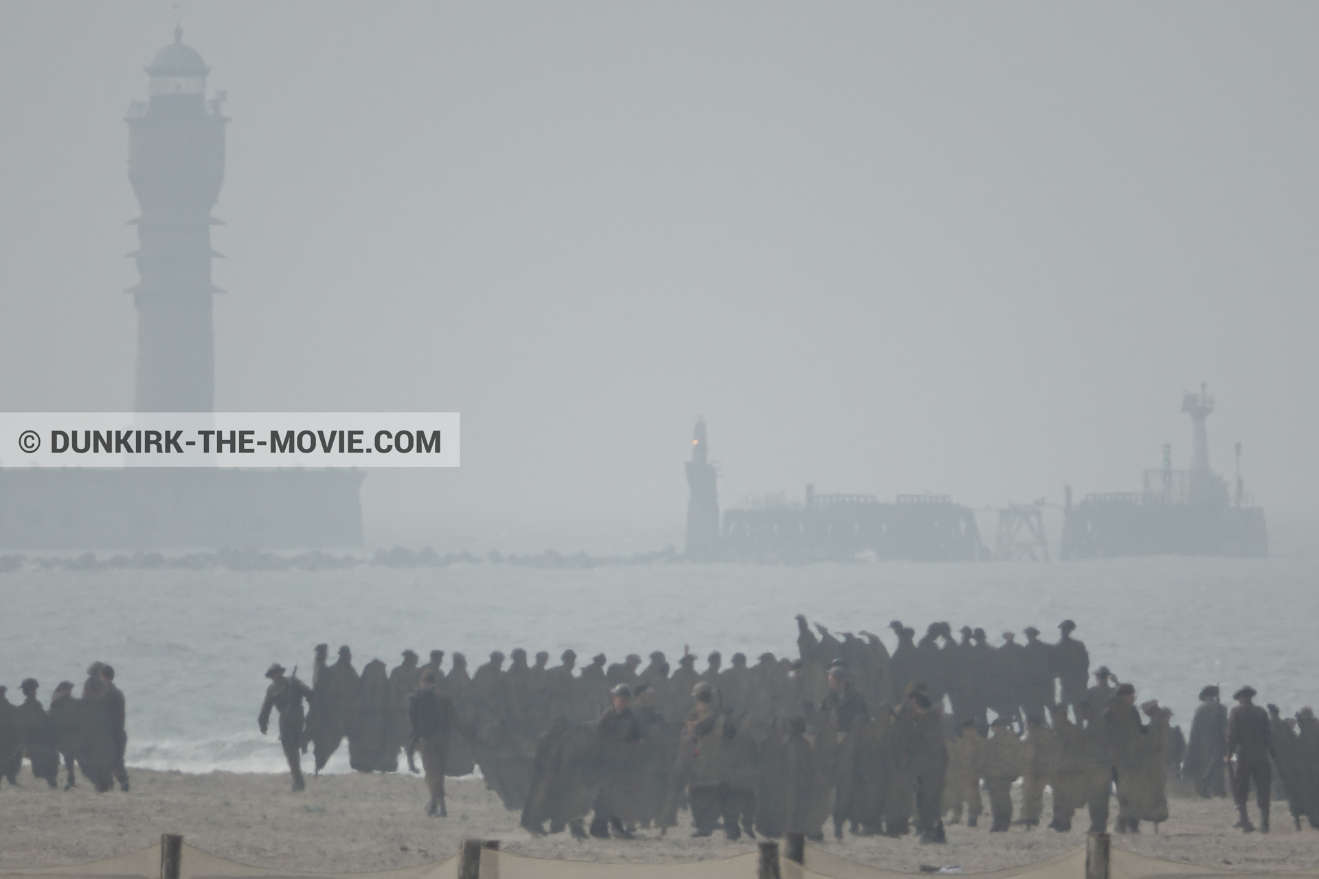Picture with grey sky, supernumeraries, St Pol sur Mer lighthouse, beach,  from behind the scene of the Dunkirk movie by Nolan