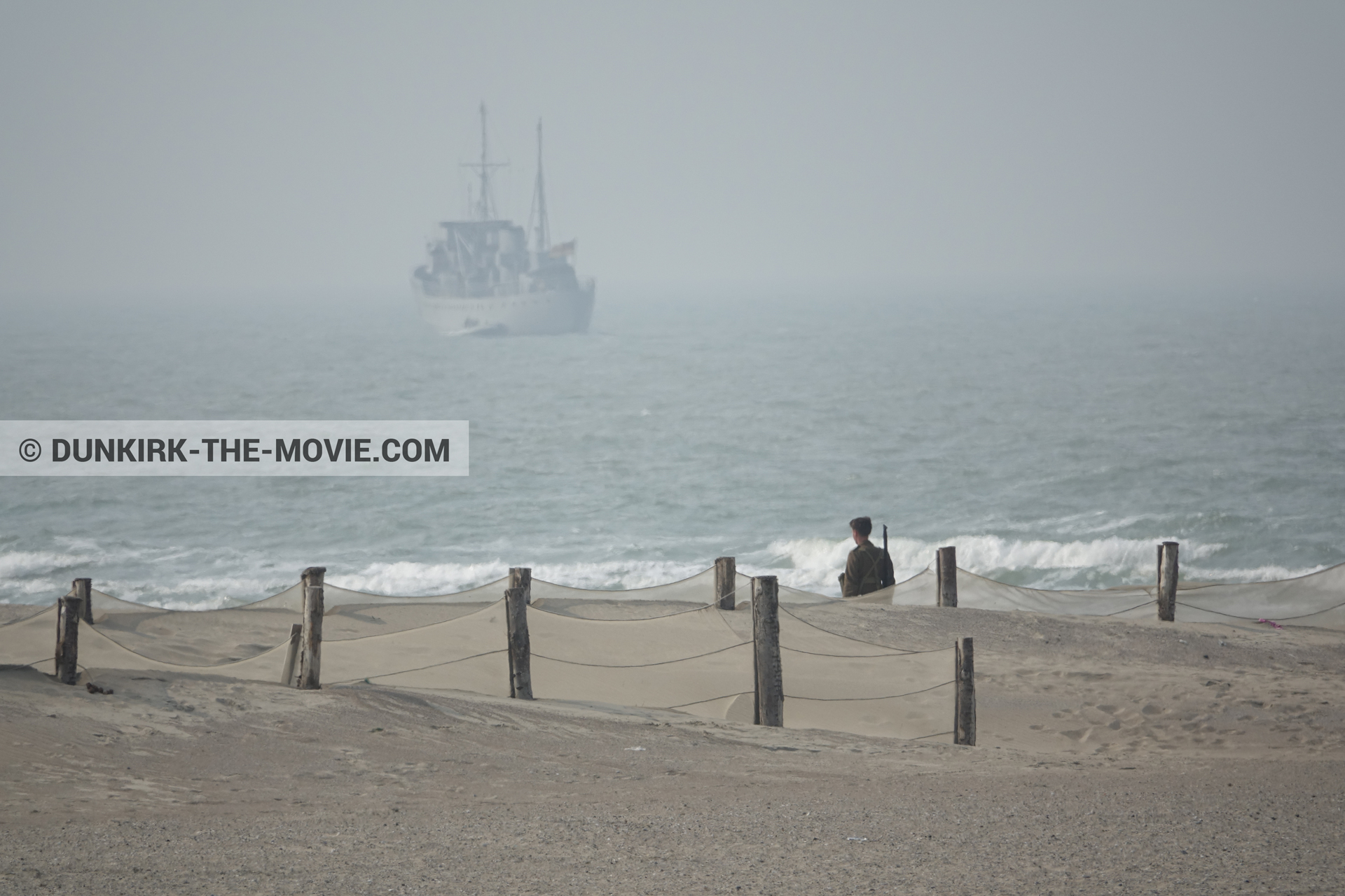 Picture with boat, grey sky, supernumeraries, rough sea, beach,  from behind the scene of the Dunkirk movie by Nolan