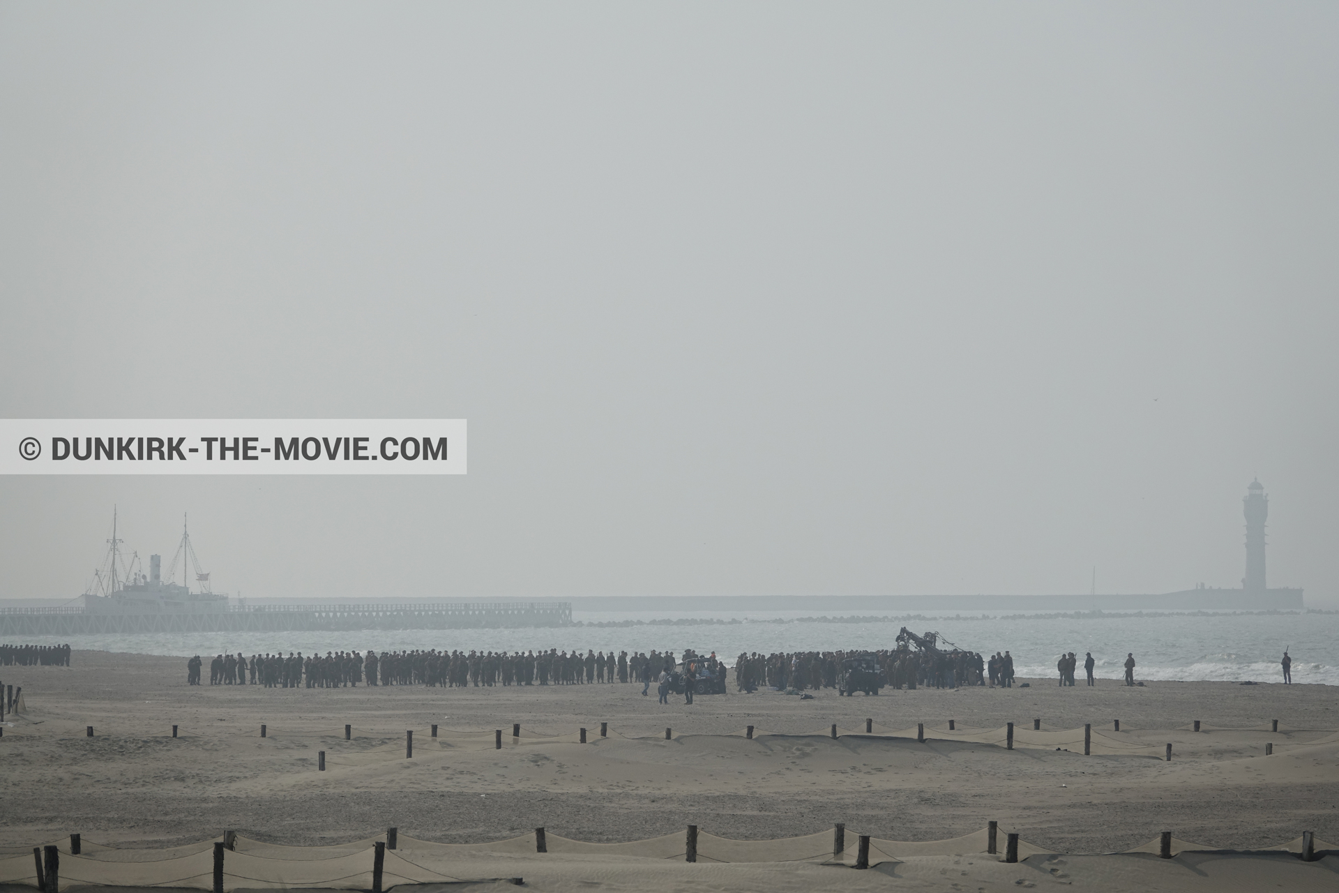 Picture with grey sky, supernumeraries, beach,  from behind the scene of the Dunkirk movie by Nolan