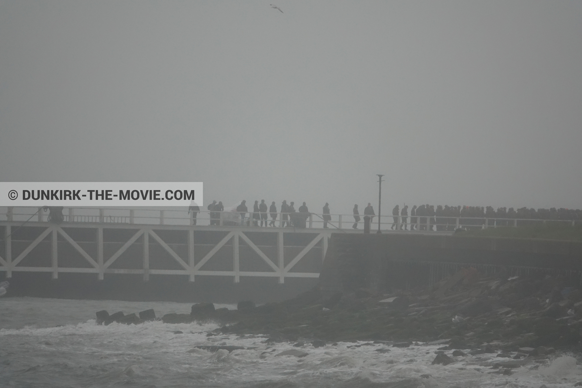 Picture with grey sky, supernumeraries, EST pier, rough sea,  from behind the scene of the Dunkirk movie by Nolan