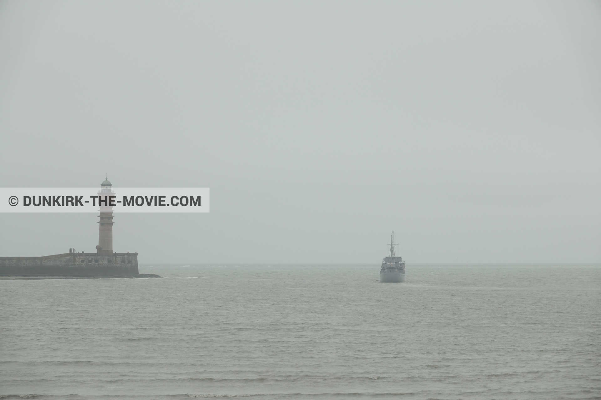 Picture with boat, grey sky, calm sea, St Pol sur Mer lighthouse,  from behind the scene of the Dunkirk movie by Nolan