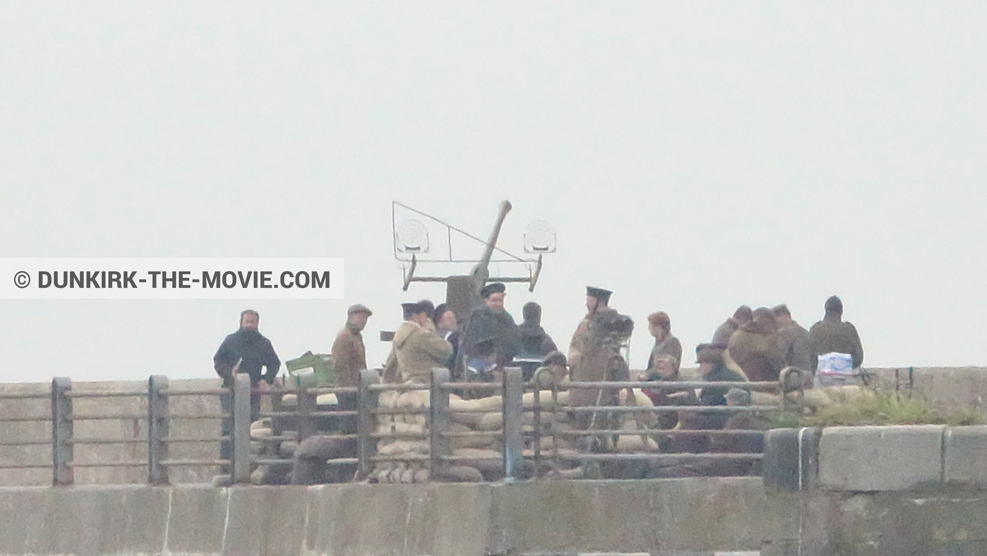 Picture with cannon, grey sky, supernumeraries, EST pier, technical team,  from behind the scene of the Dunkirk movie by Nolan
