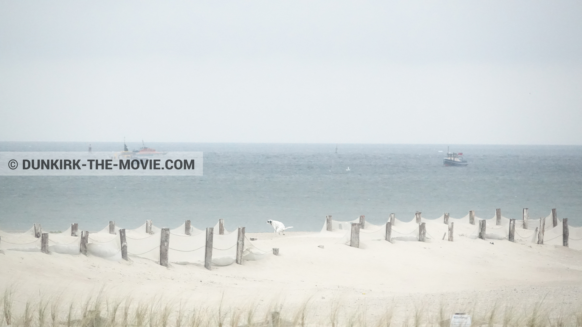 Picture with boat, grey sky, beach,  from behind the scene of the Dunkirk movie by Nolan