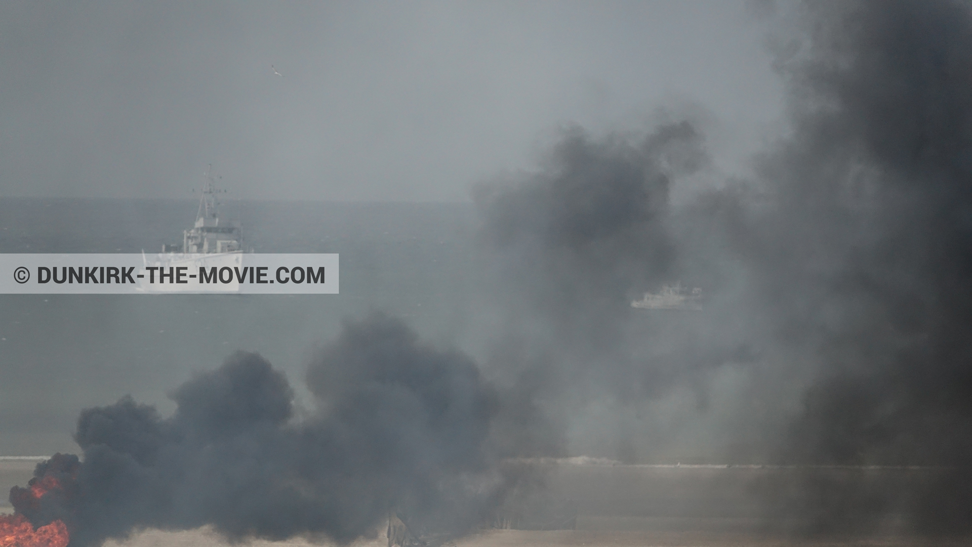 Picture with boat, black smoke, beach,  from behind the scene of the Dunkirk movie by Nolan