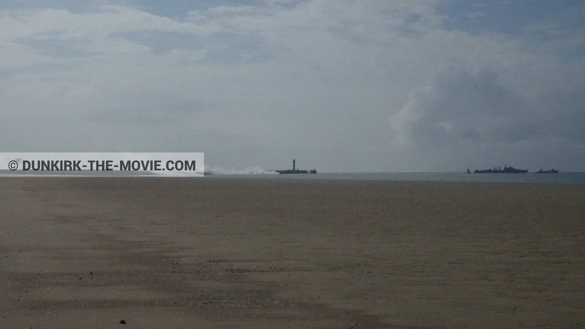 Picture with cloudy sky, white smoke, beach,  from behind the scene of the Dunkirk movie by Nolan