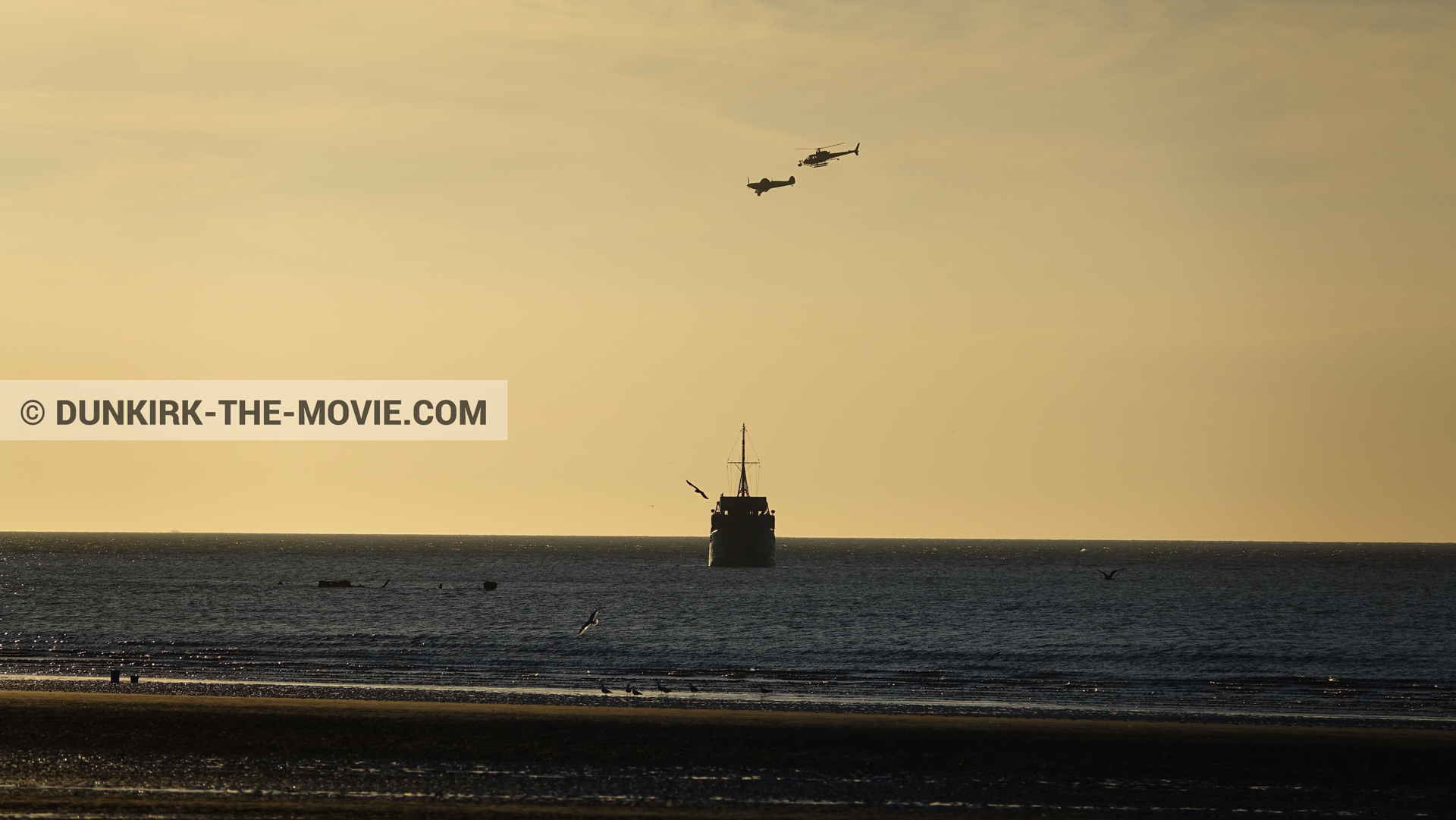 Picture with plane, boat, orange sky, helicopter camera,  from behind the scene of the Dunkirk movie by Nolan