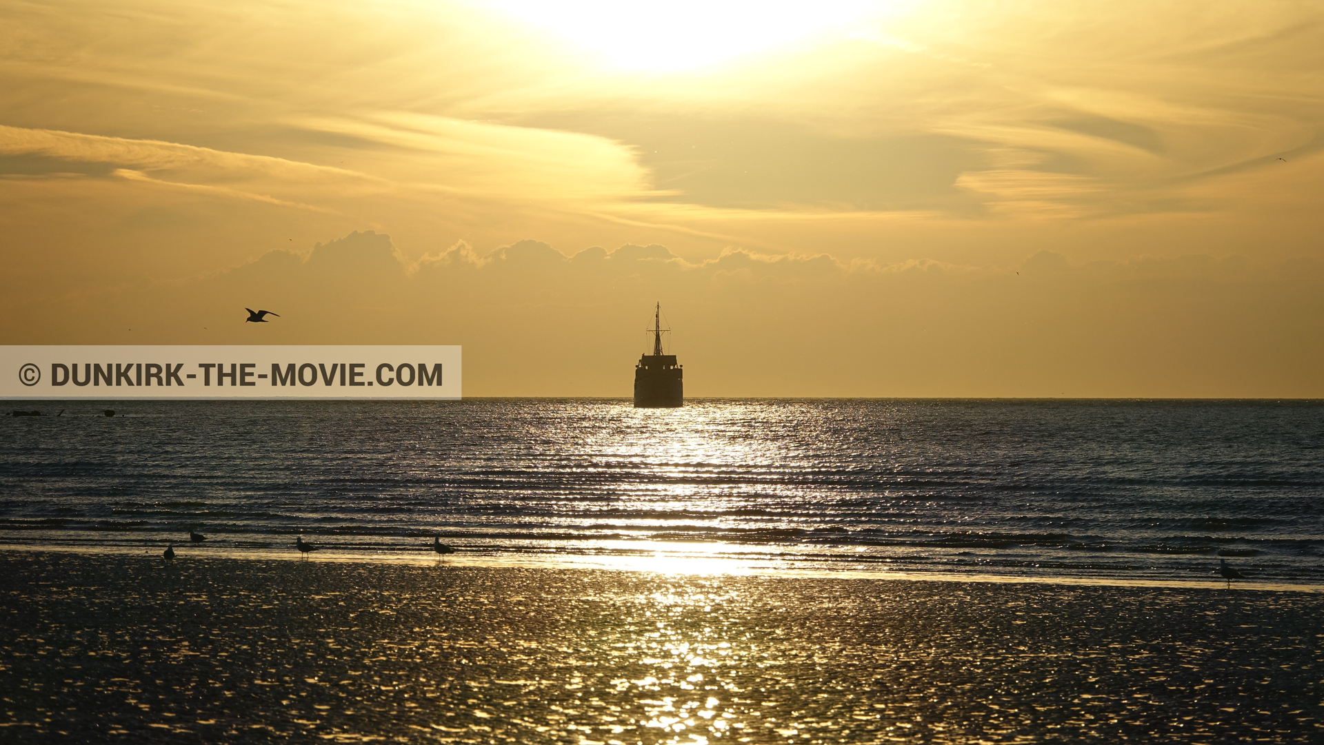 Picture with beach, calm sea, orange sky, boat,  from behind the scene of the Dunkirk movie by Nolan