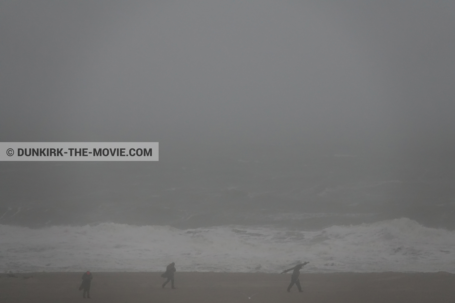 Picture with grey sky, supernumeraries, rough sea, beach,  from behind the scene of the Dunkirk movie by Nolan