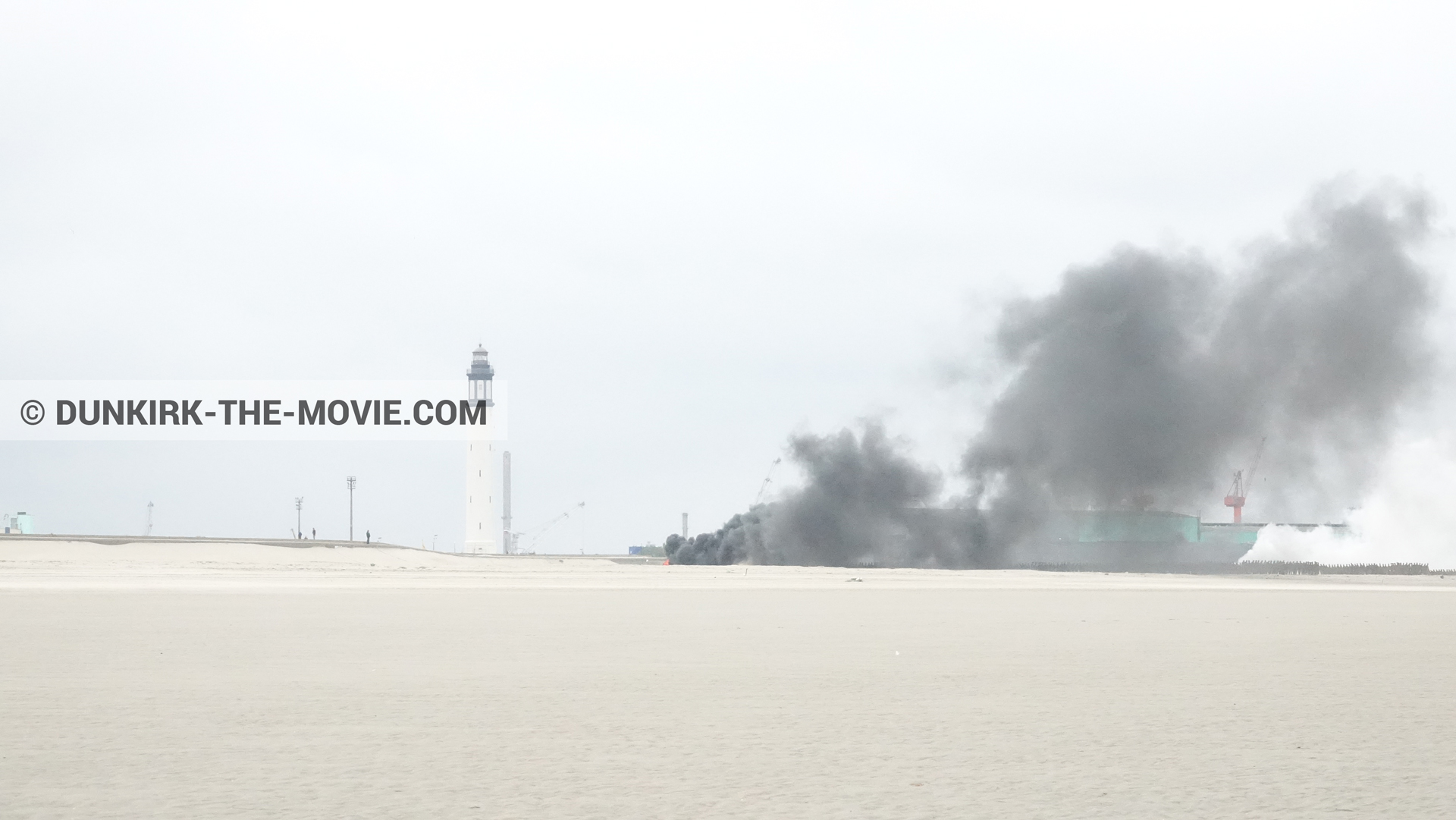 Picture with grey sky, black smoke, Dunkirk lighthouse, beach,  from behind the scene of the Dunkirk movie by Nolan