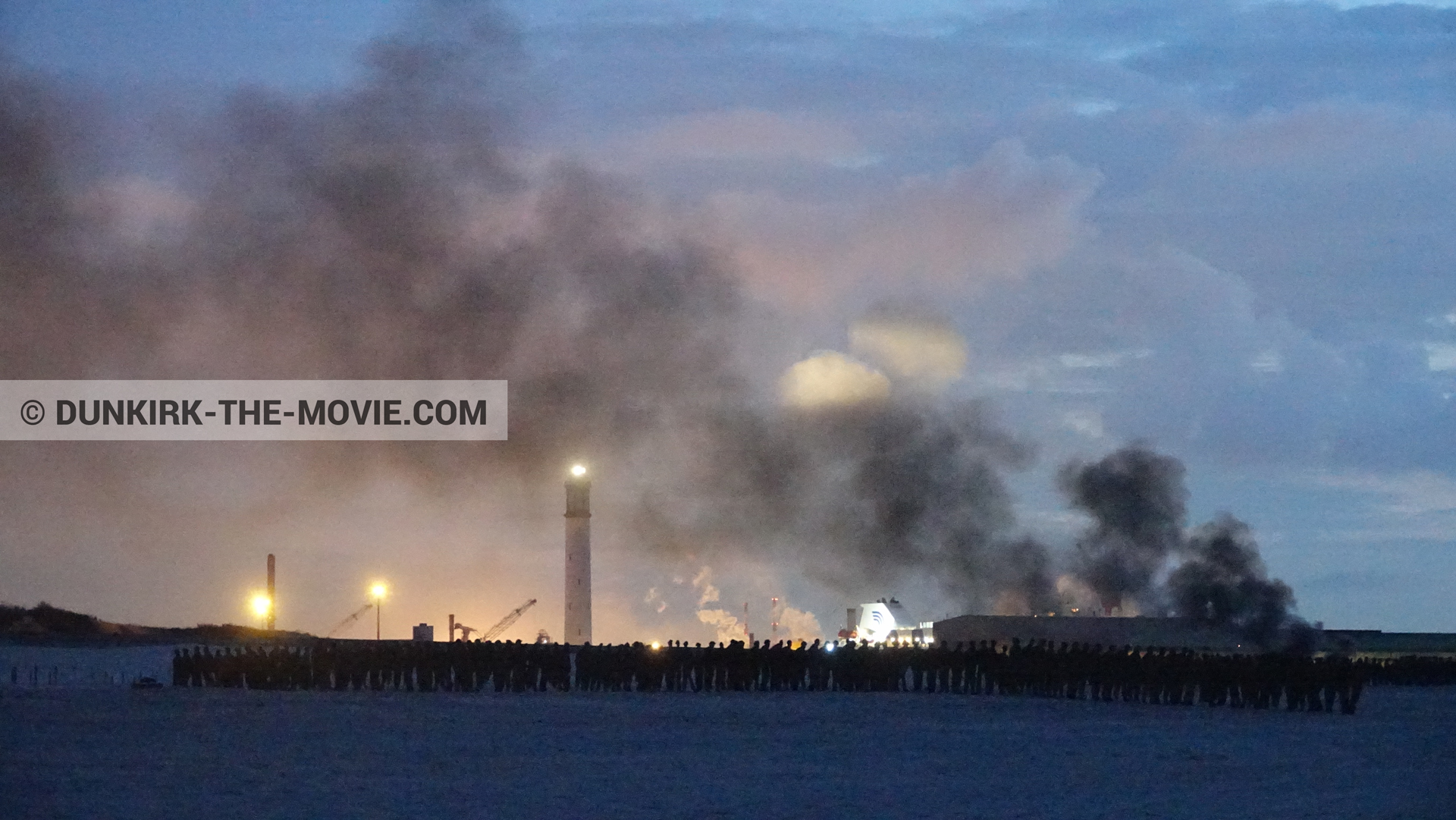 Picture with blue sky, orange sky, black smoke, Dunkirk lighthouse, beach,  from behind the scene of the Dunkirk movie by Nolan